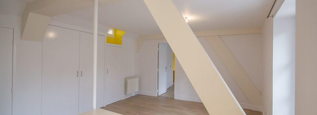 pièce de vie en blanc cassé et jaune parquet stratifié