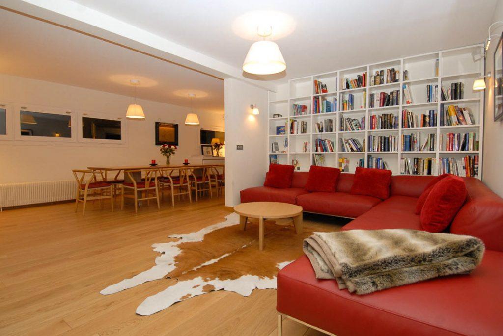 grand séjour canapé rouge et bibliothèque